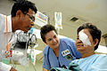 Latter-day Saints Charities volunteer nurse Jan Johnson, center, listens as a Cambodian translator speaks with a patient after cataract surgery aboard the hospital ship USNS Mercy (T-AH 19) Aug. 5, 2012, during 120805-N-GL340-017.jpg