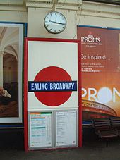"A red framed panel contains a red disc with a slightly wider dark blue band across the centre with the words ""EALING BROADWAY""."