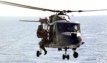 Two men in flight suits grapple on the side of a dark blue helicopter hovering over water.