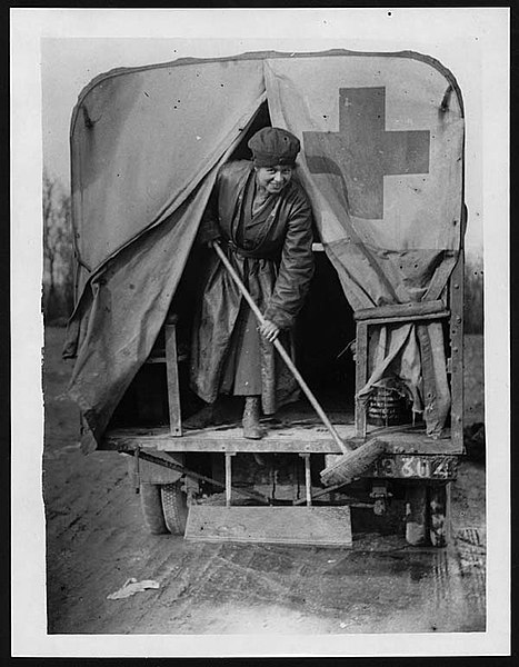 A member of the First Aid Nursing Yeomanry and her van, during World War I. This photograph unfortunately has no further information about the situation or the lady pictured. It would be interesting to know what she felt about her decision to join the First Aid Nursing Yeomanry, just at this moment. She appears to be very busy, caring for her van and has been interrupted by the photographer.  The First Aid Nursing Yeomanry was established in 1907 by Lord Kitchener to help provide communication and transport links between front line operations and larger behind the line resources. During the World War I the Corp was awarded 45 medals of honour.  [Original reads: 29. 'SCENES ON THE WESTERN FRONT. A member of the First Aid Nursing Yeomanry cleaning [caption torn, word/s missing] car.']  digital.nls.uk/74548576