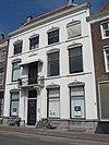 foto van Huis met brede lijstgevel en schilddak aan de straat