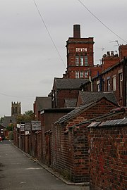 Oldham's irregularly constructed built environment is characterised by its red-brick cotton mills and surrounding terraced houses.