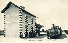 Carte postale ancienne sépia représentant un bâtiment et un train.
