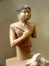 Bust and head of a pharaoh holding a flail.