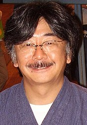 A 46-year-old Japanese man smiling directly into the camera. He has black hair going to gray around the temples and a graying mustache.