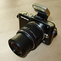 A black Olympus PEN E-PL3 with the standard flash attachment and 14-42mm lens fitted
