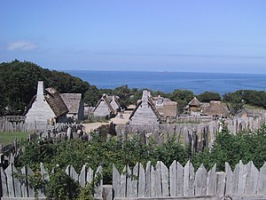 A modern day photograph of a village consisting of small, primitive wooden houses.  Most of the houses have thatched roofs.  In the distance is a large expanse of ocean and a clear blue sky.  The village is surrounded by a wall consisting of tall, thick wooden planks.