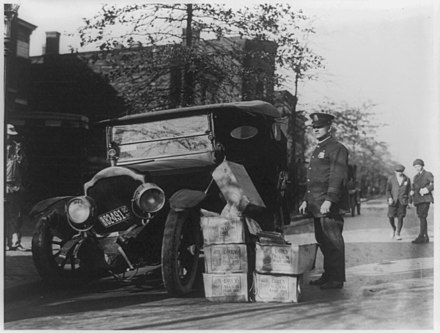A policeman with wrecked automobile and confiscated moonshine, 1922 Policeman and wrecked car and cases of moonshine.jpg