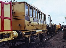 Ornate railway carriages and a small yellow locomotive