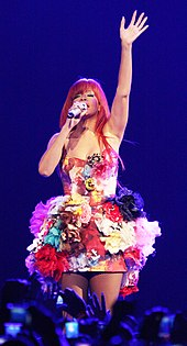 Rihanna with red, long hair and a dress with floral patterns. Her left hand is raised and her right hand holds a microphone near her mouth.