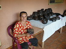Doña Rosa Brítez with her blackware pottery seated on plastic chair