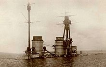 The top of a warship juts out of calm water after it had been sunk