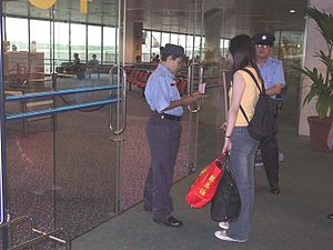 SATS Security Services - SATS auxiliary police officers performing visa and travel document checks at Singapore Changi Airport.