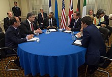 A group of men and women is Western business attire sit around a circular table with a blue tablecloth.