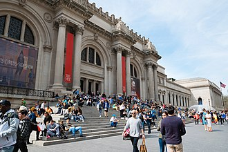 Metropolitan Museum of Art - Facade of imposing building with Greek columns. Large colored banners hang from the building's top.