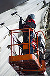 U.S. Navy Seaman Jordan Garrett, foreground, and Ship's Serviceman Seaman Kyle Humphreys paint the hull of the aircraft carrier USS George Washington (CVN 73) in Yokosuka, Japan, Jan. 1, 2014 140101-N-XK455-001.jpg