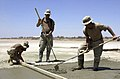 US Navy 030429-N-2517J-003 Seabees from Naval Mobile Construction Battalion One Thirty Three (NMCB-133) smooth the surface of newly poured concrete slab, using a screed board and rakes, during repair and improvements for the ru.jpg