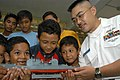 US Navy 030505-N-0021M-001 Information Systems Technician 1st Class Frank Agcaoili shows residents of the Jamiyah Children's Home a model of the guided missile cruiser USS Bunker Hill (CG 52).jpg