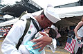 US Navy 030529-N-3642E-001 Airman Andy Nunez kisses his newborn son for the first time after returning from deployment aboard USS Theodore Roosevelt (CVN 71).jpg