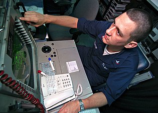 US Navy 031230-N-9742R-001 Electronic Warfare Supervisor, Crytpologic Technician 3rd Class Daniel Martin, from Bartlett, Ill., monitors the ship's Advanced Combat Direction System console in the Combat Direction Center.jpg