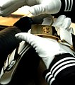 US Navy 040220-N-6213R-008 Airman Pedro Feliciano, of Philadelphia, Pa., shines his belt buckle while traveling to a performance as a member of the U.S. Navy Ceremonial Guard.jpg