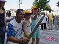 US Navy 040731-N-6243C-001 Lt. Cmdr. Demetries A. Grimes poses for a picture with young Olympic fans. Grimes, a Greek-American, ran in the torch relay held in Larissa, Greece, on Saturday, July 24, 2004.jpg