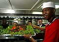 US Navy 041225-N-4953E-031 Culinary Specialist Seaman Demarcos Blow displays the Christmas Turkey before the crew enjoys Christmas dinner aboard the guided missile cruiser USS Monterey (CG 61).jpg