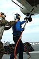 US Navy 050110-N-9222M-047 Lance Cpl. Chris Seigal, left, assists Airmen Apprentice Grigory Severyukhin hook a cargo pendant onto the cargo hook of an SA-330 Puma helicopter on the flight deck of USS Essex (LHD 2).jpg