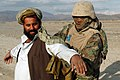 US Navy 050113-A-9607R-060 Hospital Corpsman 2nd Class Neville Parris, assigned to Weapons Company, 3rd Battalion, 3rd Marine Regiment, searches an Afghan man at a vehicle check point.jpg