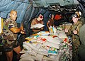 US Navy 050124-N-0168J-004 Multinational forces move bags of rice onto a MH-53 Sea Dragon helicopter during a joint working party.jpg