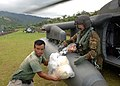 US Navy 051016-N-5526M-048 U.S. Army Specialist Ryan Becker helps unload food, water, and medicine from a UH-60 Blackhawk helicopter during relief efforts.jpg