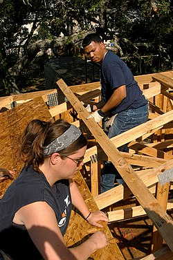Atlantic Beach, Fla. (May 19, 2006) - Gunner's Mate 2nd Class Amy Hamilton, left, and Machinist's Mate Fireman Andy Gomez help build a house on a Beaches Habitat construction project. Sailors from the conventionally powered aircraft carrier USS John F. Kennedy (CV 67) volunteered to help those in need of a home. The construction site is part of a local Habitat for Humanity chapter, where community volunteers help build homes for those in need. U.S. Navy photo by Photographer's Mate 3rd Class Adam Herrada.