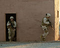 US Navy 071210-M-6020M-005 A Marine and Sailor, both assigned to Marine Wing Support Squadron (MWSS) 374, search a building in a simulated combat town during Desert Talon 1-08.jpg