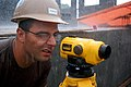US Navy 090424-N-1057H-466 Engineering Aide Constructionman Travis C. Porter takes measurements in the rain during construction at the Hamramba School Project.jpg