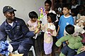 US Navy 091027-N-3830J-336 Cryptologic Technician (Technical) 1st Class Marvin Jefferson, assigned to the amphibious command ship USS Blue Ridge (LCC 19), hands out toys to children at the Praise Emmanuel Children's Home.jpg