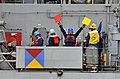 US Navy 100319-N-4774B-016 Merchant Mariners aboard the Military Sealift Command fast-combat support ship USNS Rainier (T-AOE 7) signal to Sailors aboard the guided-missile cruiser USS Bunker Hill (CG 52).jpg
