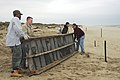 US Navy 100409-N-9180M-026 Senior Chief Culinary Specialist Stephen Wilson, left, Aviation Structural Mechanic 2nd Class Patrick Price, a Navy dependent and Navy Counselor 1st Class Chad Reints move debris off the beach.jpg