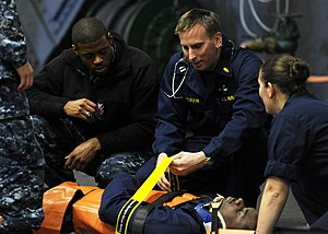 US Navy 120213-N-VA840-165 Lt. Brian W. Ferguson, center, secures a Sailor to a stretcher during a medical drill aboard the aircraft carrier USS Ge.jpg