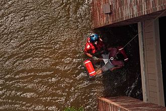 United States Coast Guard - A Coast Guard Aviation Survival Technician assisting with the rescue of a pregnant woman during Hurricane Katrina in 2005.