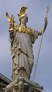 A neoclassical statue of Athena stands in front of the Austrian Parliament Building in Vienna.