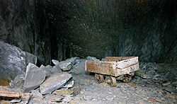 A truck once used for tipping waste stands abandoned in a slate mine near Llangollen