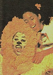 Young man in lion costume kneels in front of young girl with pigtails, both singing