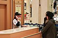 Woman agent wearing the winning NPB Baseball team's cap and uniform at the reception desk of the Department store.jpg