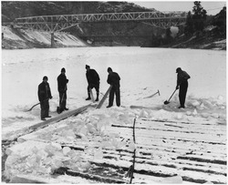 Workmen cutting ice around a raft of wood piling, showing the thickness of ice which formed during February - NARA - 294247.tif