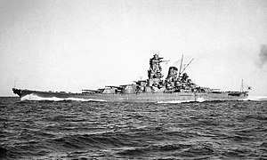 A large warship with a tall, pagoda-like superstructure, single funnel and multiple gun turrets, steaming in the open ocean.