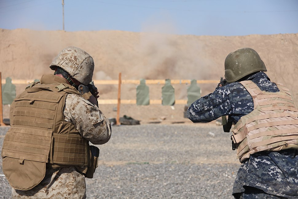A Marine (left) and a sailor (right) both dressed in combat gear, fire at a target on a desert weapons range