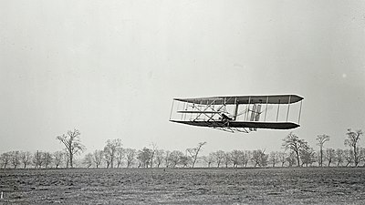 Orville in flight over Huffman Prairie, in Wright Flyer II. Flight #85, approximately 1,760 feet (536 m) in 40 1/5 seconds, 16 November 1904.