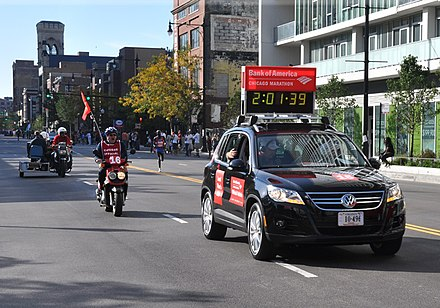 Evans Cheruiyot follows the course car (with clock) during his 2008 victory. The lead course car carries the current race time. 20081012 Evans Cheruiyot follows pace car.jpg