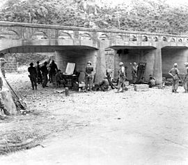 A group of soldiers around a makeshift office under a bridge