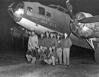 """Operation Frantic - A B-17 crew poses with their plane. The nose art on the bomber reads """"Polar Star"""" (likely referring to the star Polaris) in Russian."""